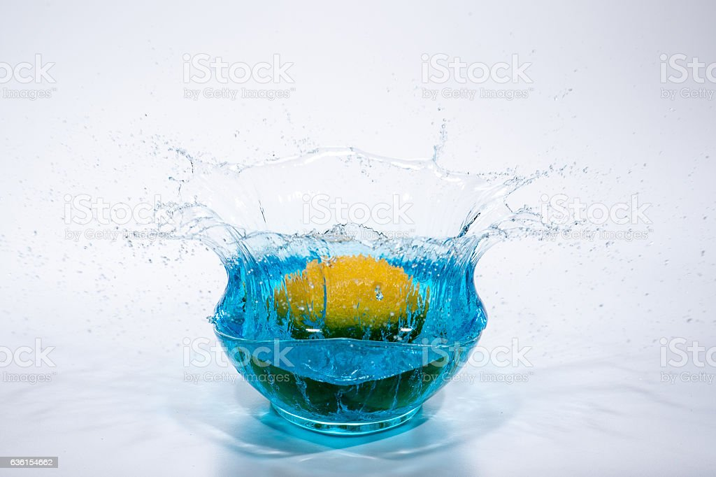 Citrus falling and splashing in a glass bowl stock photo