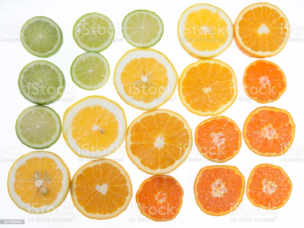 Citrus fruit arranged in a tonal color gradient on white background stock photo