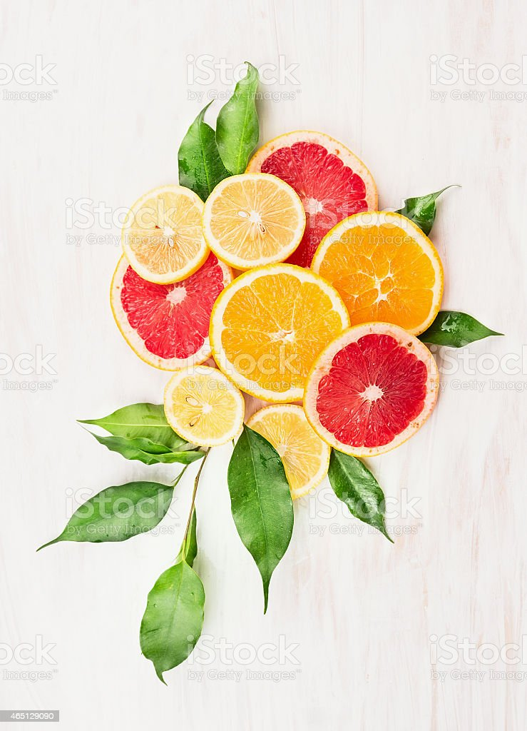 Citrus fruits composing with green leaves on white wooden background stock photo