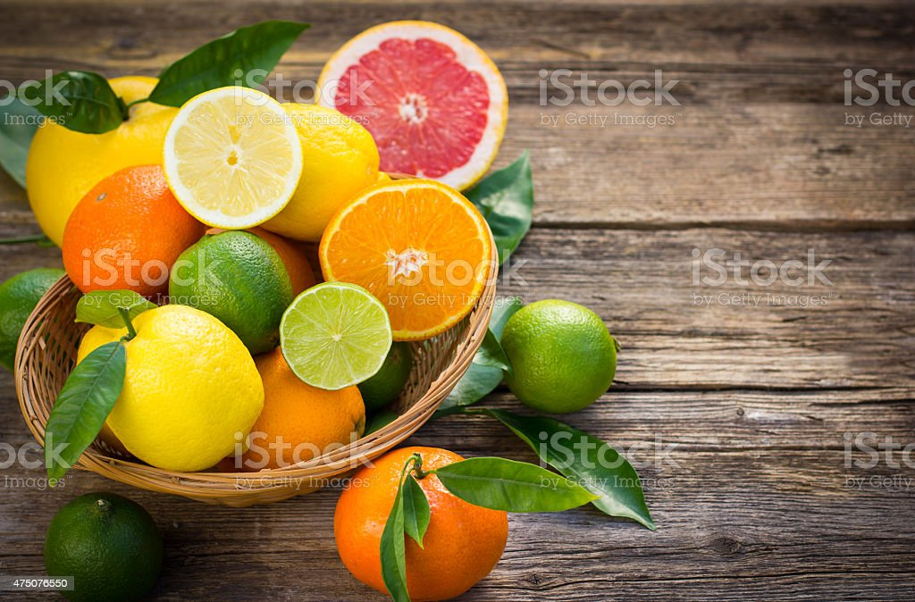 Citrus fruits in the basket on the rustic table stock photo