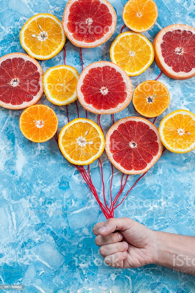 Citrus in conjunction as balloons, hand holding the strings. stock photo