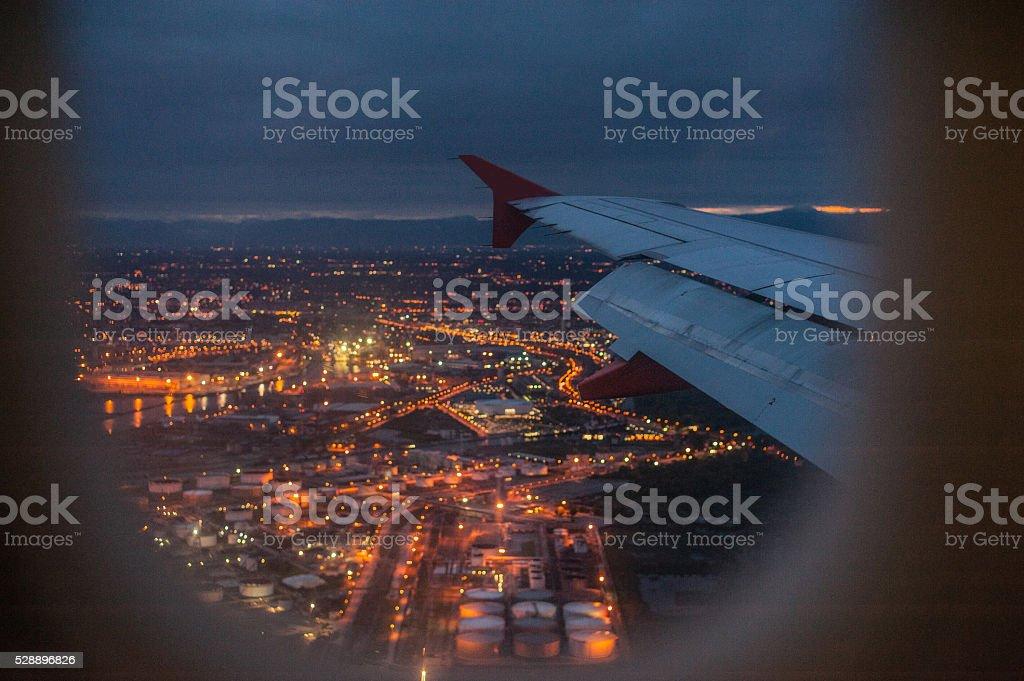 City at night through airplane window stock photo