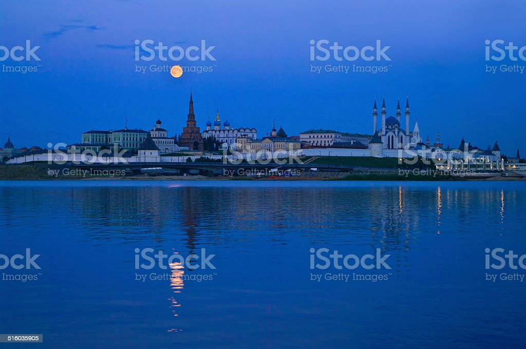 city at night with full moon stock photo