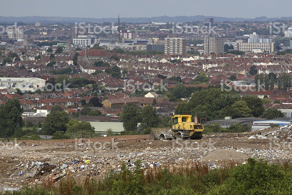 City behind garbage being processed by bulldozer on landfill site royalty-free stock photo