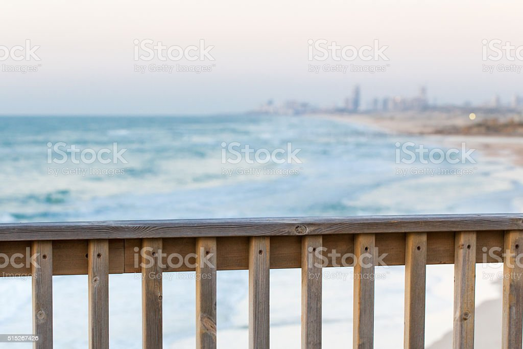 City buildings sea shore wooden fence view, sunset. stock photo