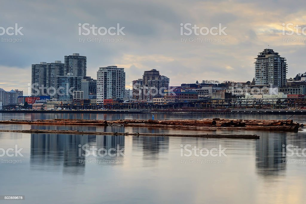 city by the river at sunset stock photo