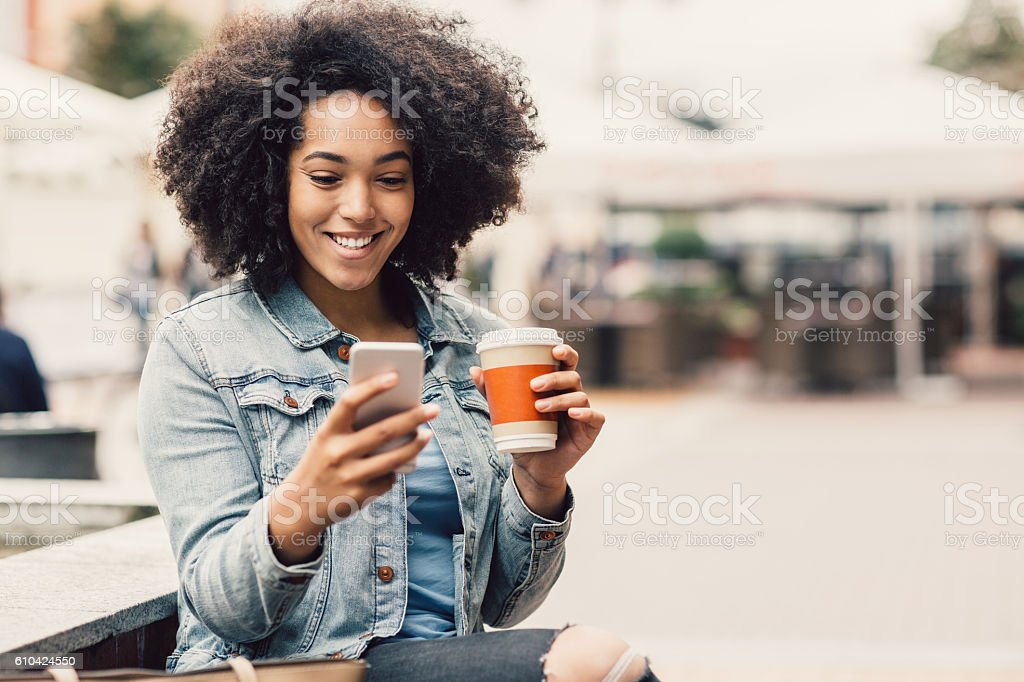 City girl with smart phone and coffee cup stock photo