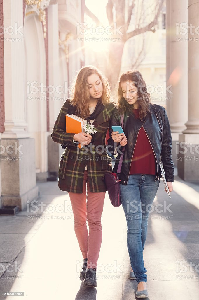 City girls on a leisure walk texting on smartphone stock photo