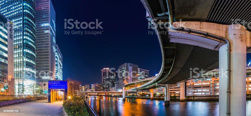 City highway curving through modern skyscrapers illuminated night Osaka Japan stock photo