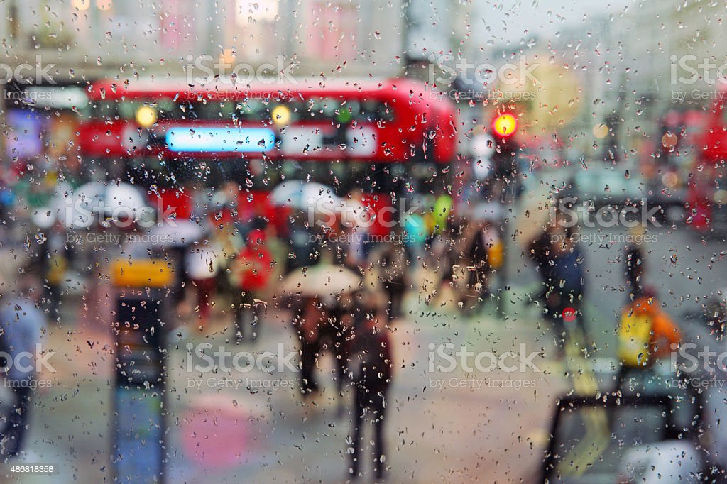 City life in a rainy day: people walking with umbrellas stock photo