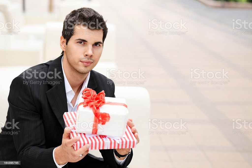 City life series: young businessman holding gifts stock photo