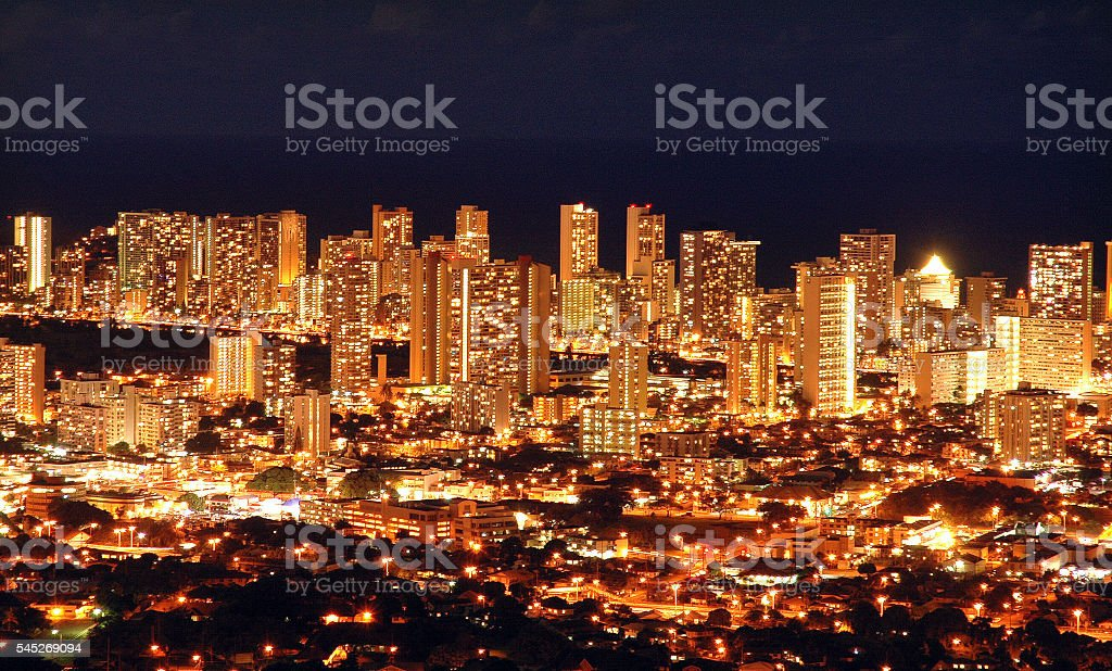 City lights of Honolulu at night against ocean stock photo