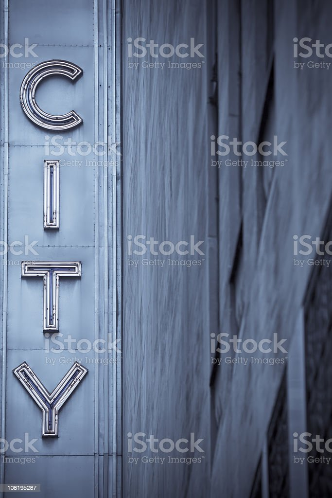 city neon sign with building in blue tones stock photo