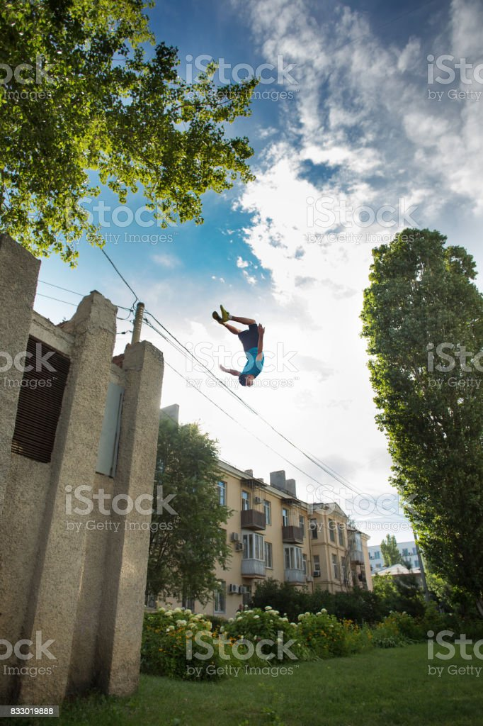 City parkour. The guy does the opposite somersault. Shooting from a...