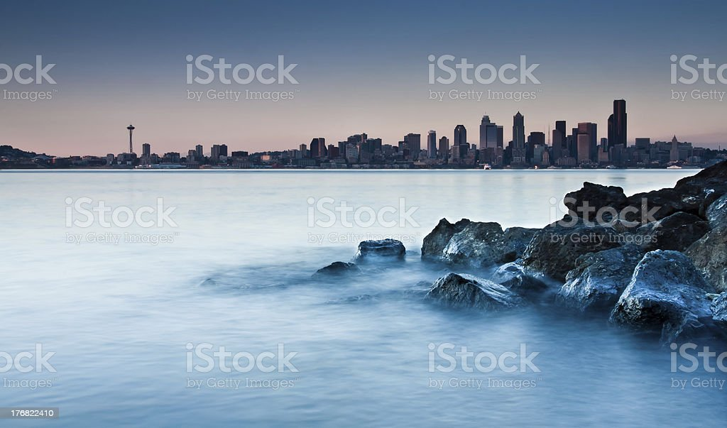 city skyline from a rocky beach stock photo