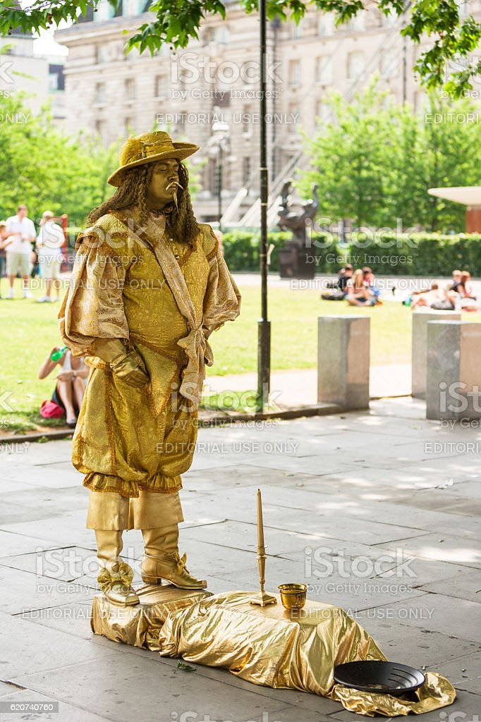 City street performance of gold painted actor. London, UK royalty-free stock photo