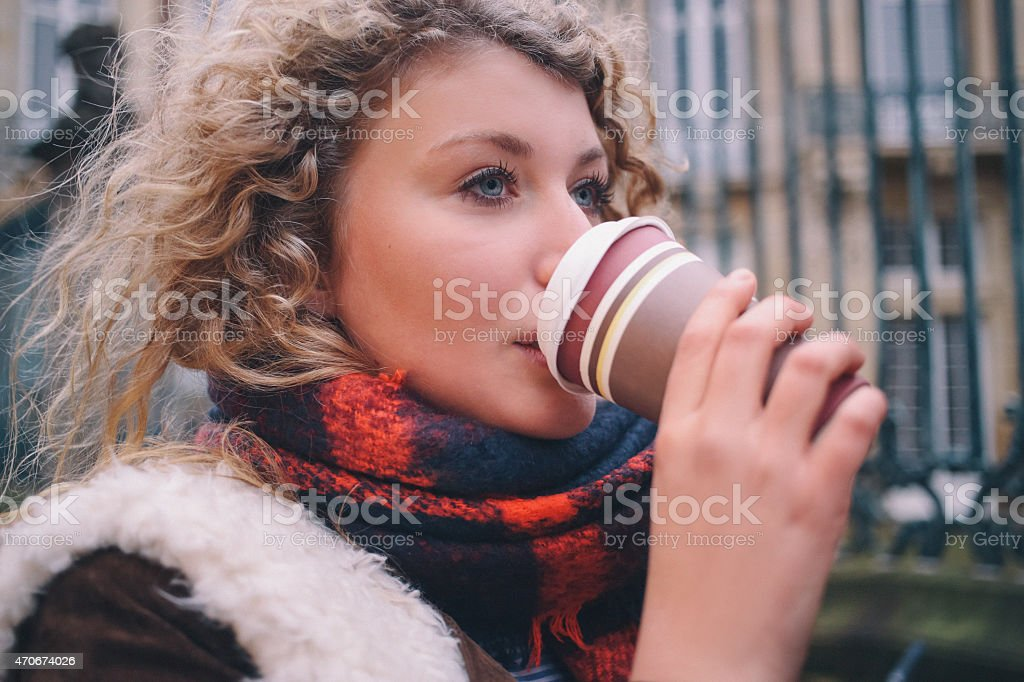 City student sipping a takeaway coffee on a winter day stock photo