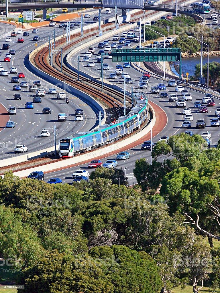 City transit: Metro train travelling down freeway median strip stock photo