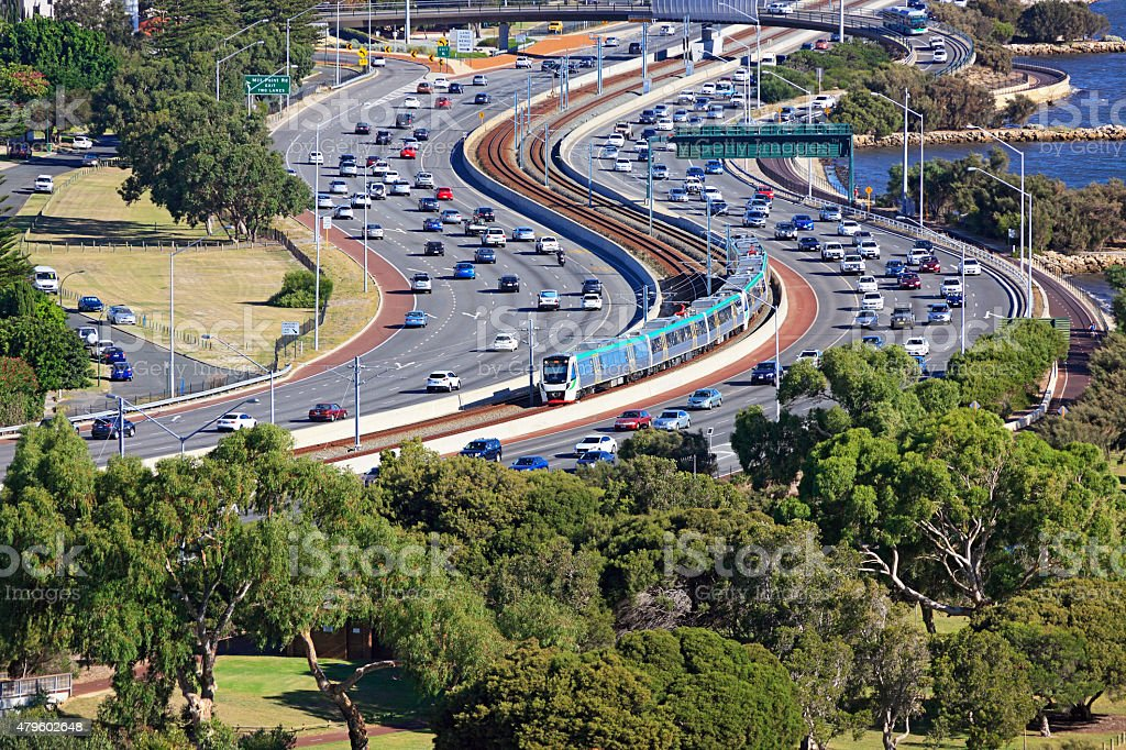 City transport: electric train travels down middle of busy freeway stock photo