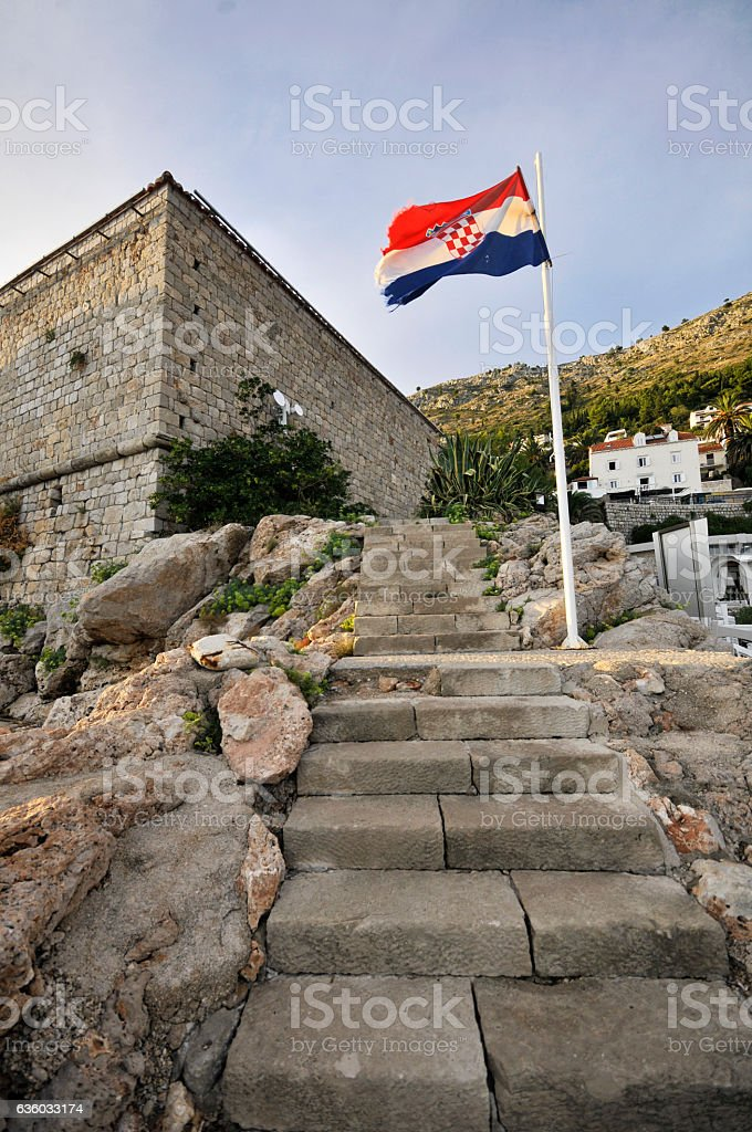 City walls of Dubrovnik and the Croatian flag stock photo