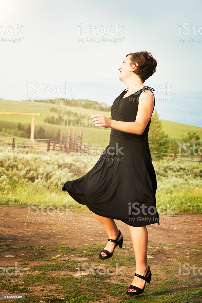 City woman dancing with joy stepping in rural land stock photo