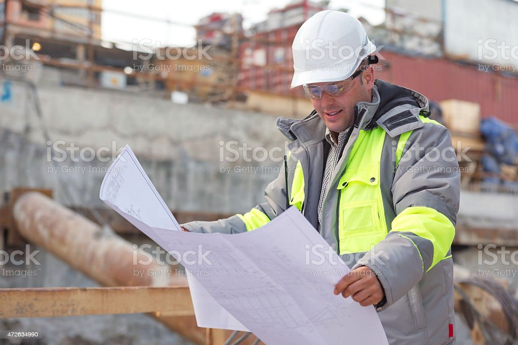 Civil engineer at construction site looking at designs stock photo