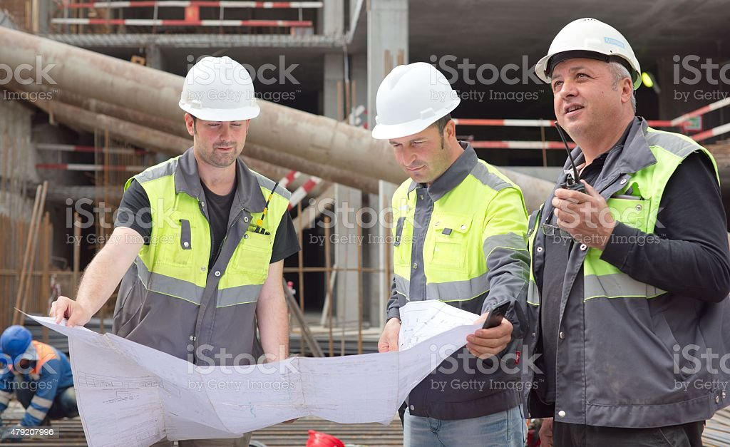 Civil Engineers And Senior Foreman At Construction Site stock photo