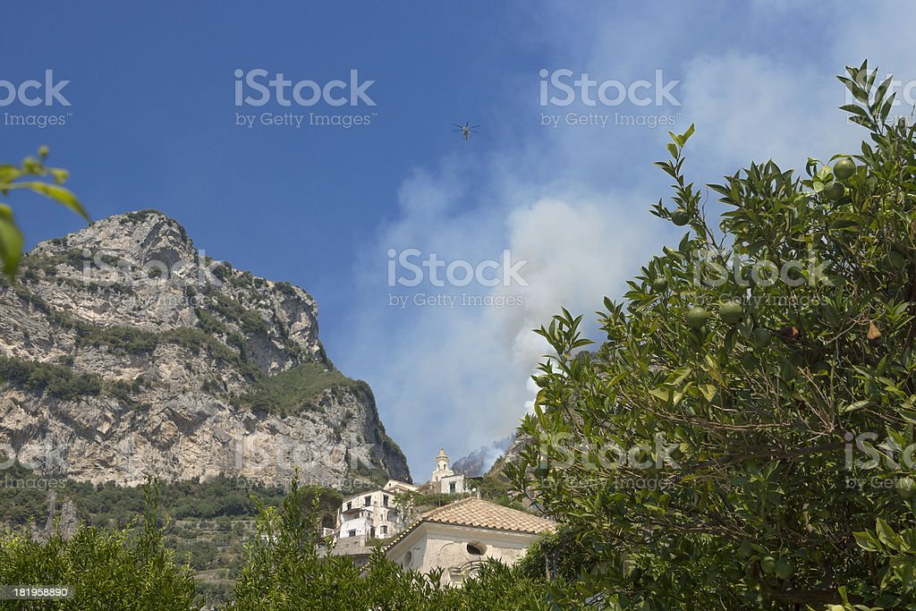 Civil protection helicopter over an Amalfi Coast hill in flames royalty-free stock photo