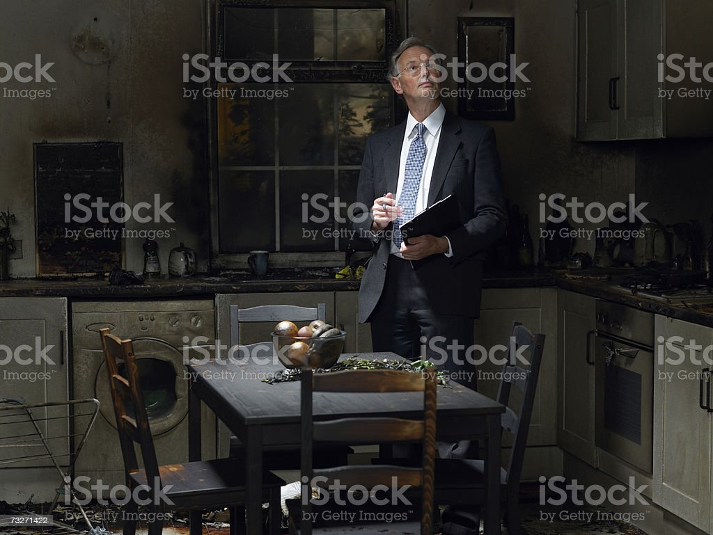Claims adjuster inspecting kitchen damaged in fire stock photo