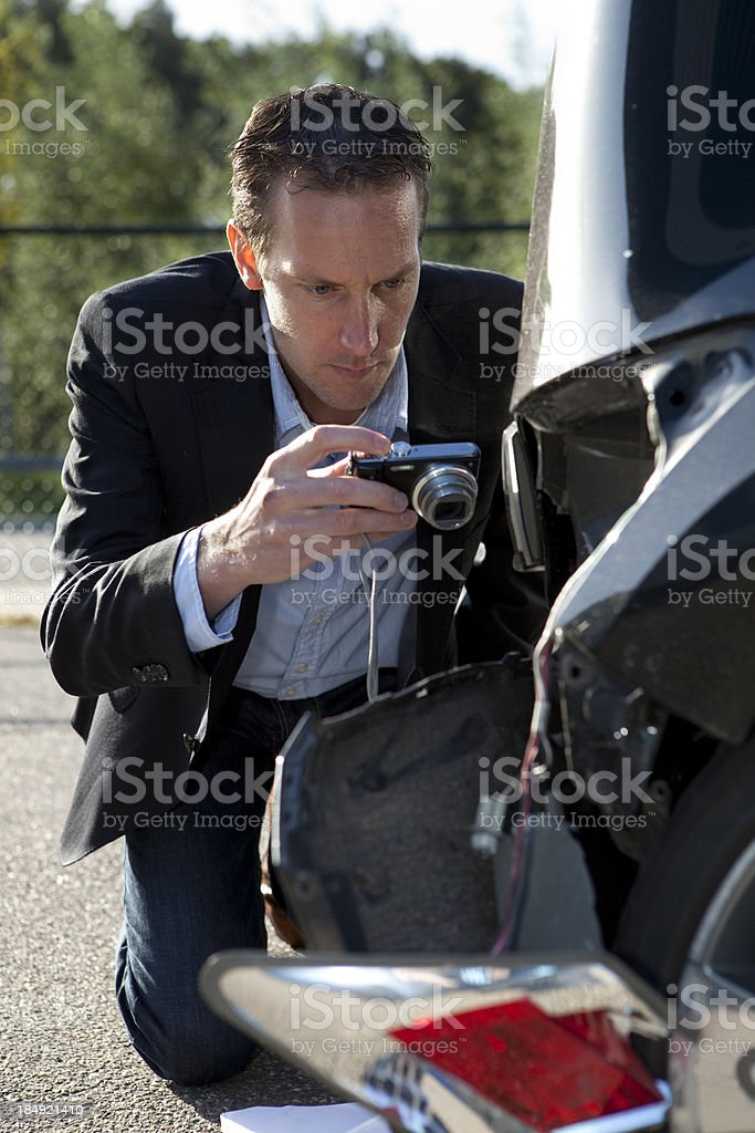 Claims adjuster taking picture of dameges car royalty-free stock photo