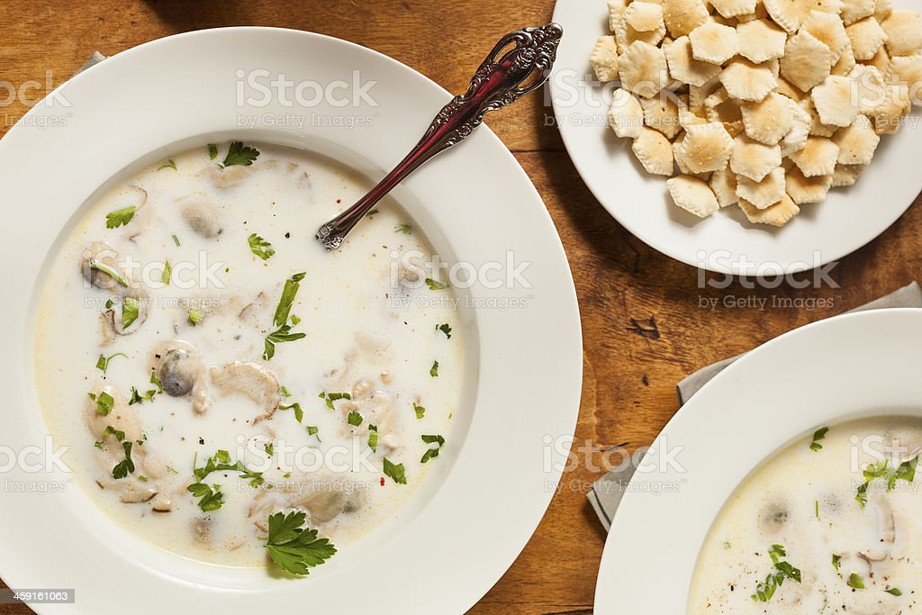 Clam chowder with parsley garnish and oyster crackers stock photo
