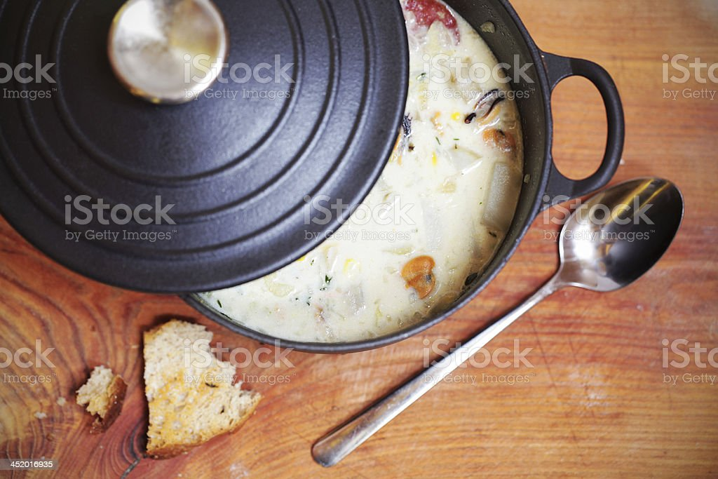 Clam chowder with sausage and potatoes in iron casserole stock photo