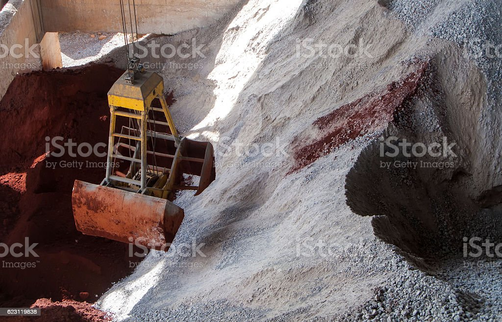 Clam Shell grab on ore pile stock photo