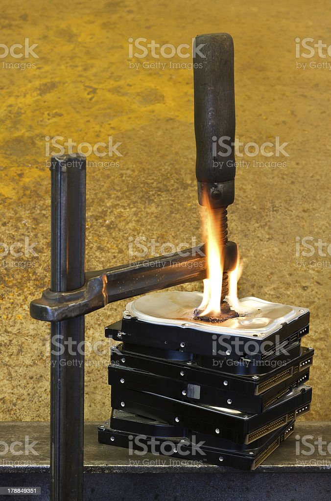 clamp pressing on burning stack of hard drives royalty-free stock photo