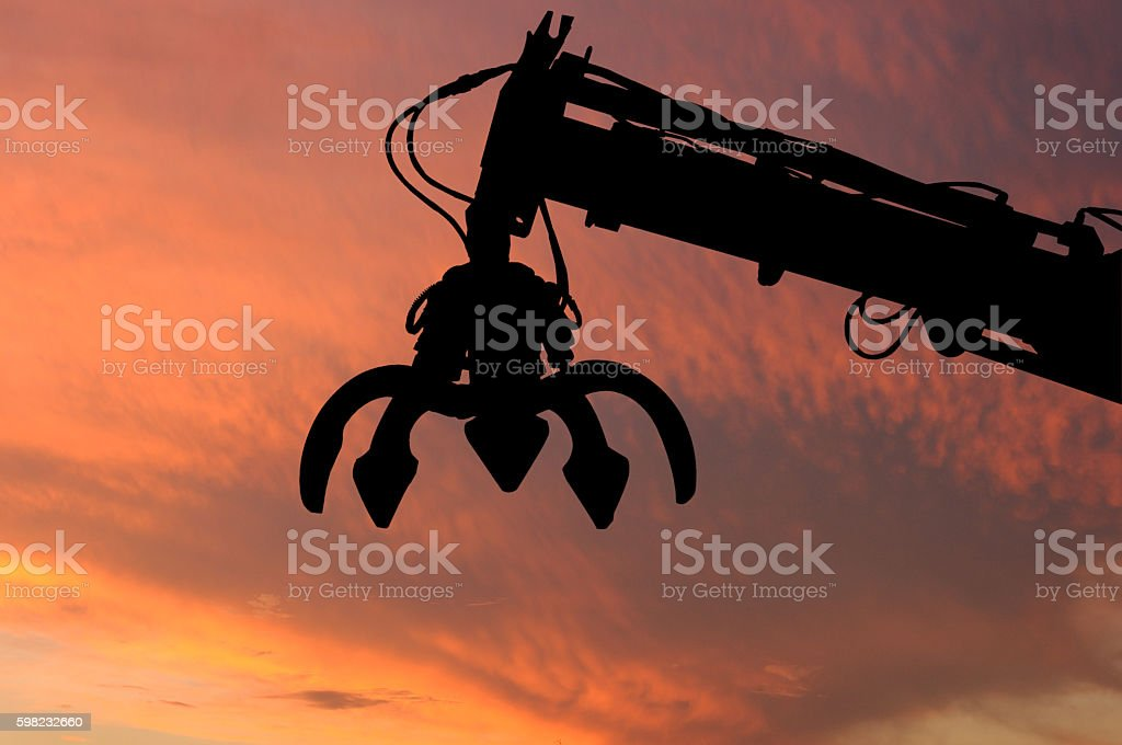 Clamshell and Hydraulic crane shillouette with evening light sky stock photo