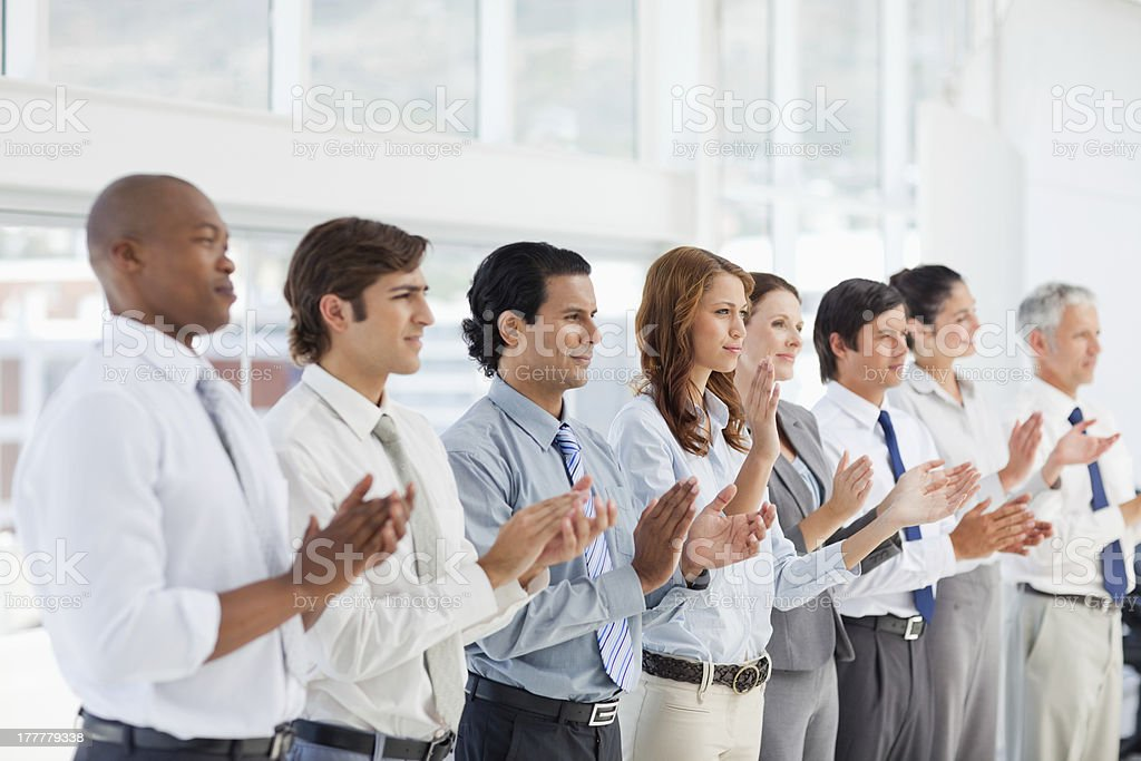 Clapping business people in a line royalty-free stock photo