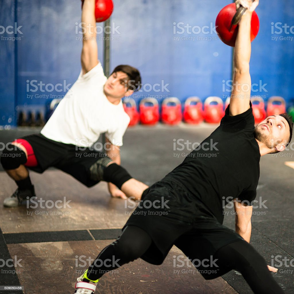 class lifting a kettlebell in a gym stock photo