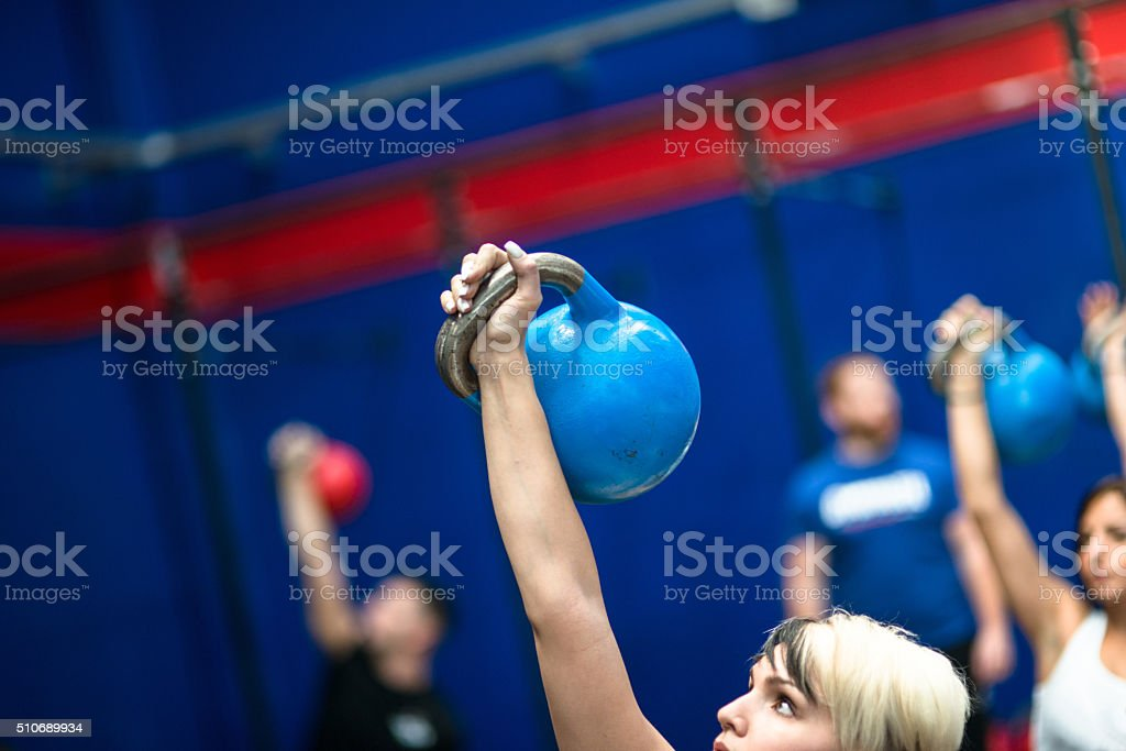 class lifting a kettlebells in a gym stock photo