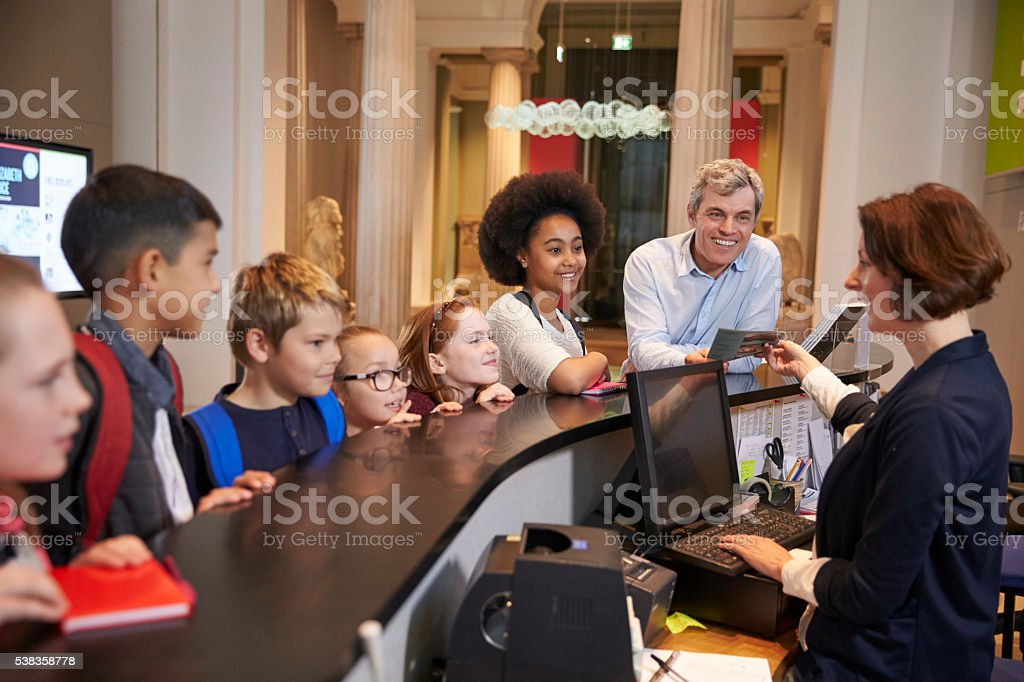 Class On School Trip Buying Entry Tickets To Museum stock photo