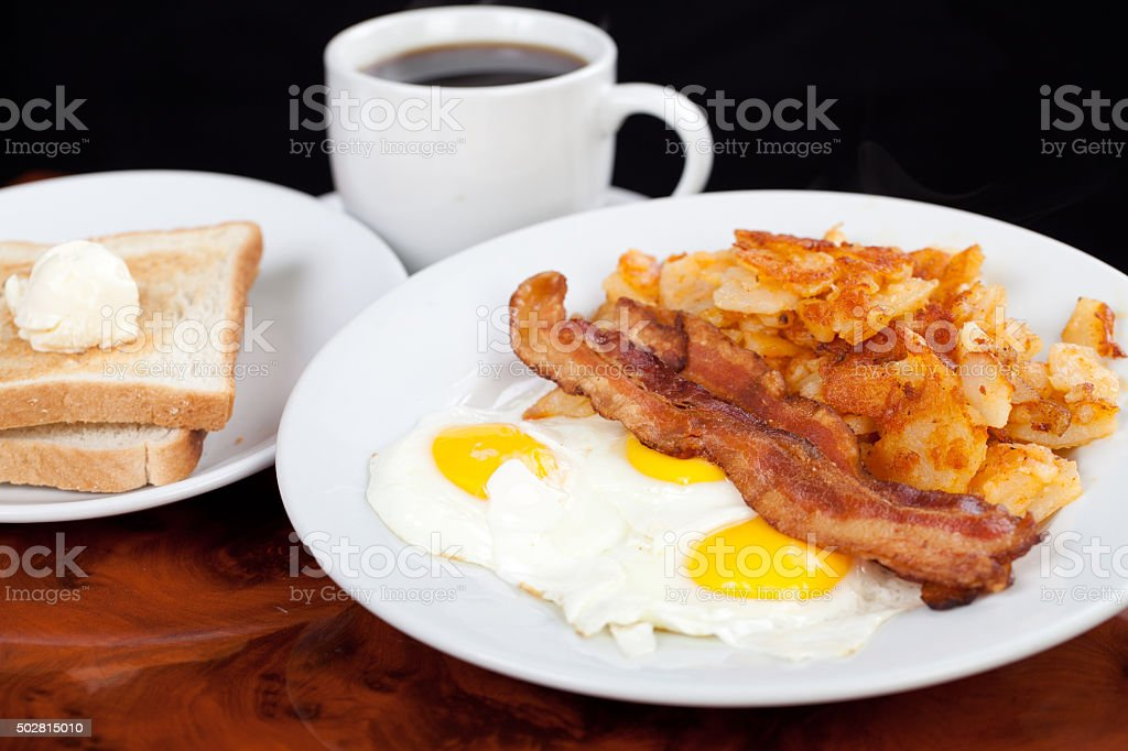 Classic American breakfast eggs beacon potatoes toast and coffee stock photo