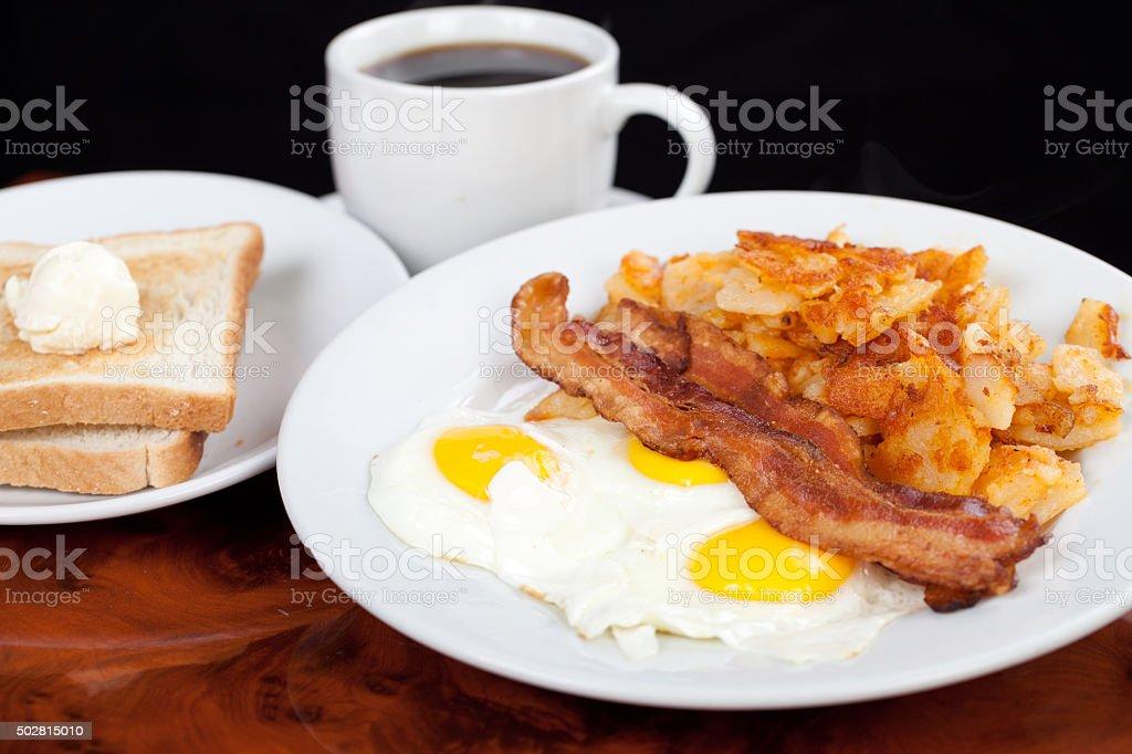 Classic American breakfast eggs beacon potatoes toast and coffee stock photo
