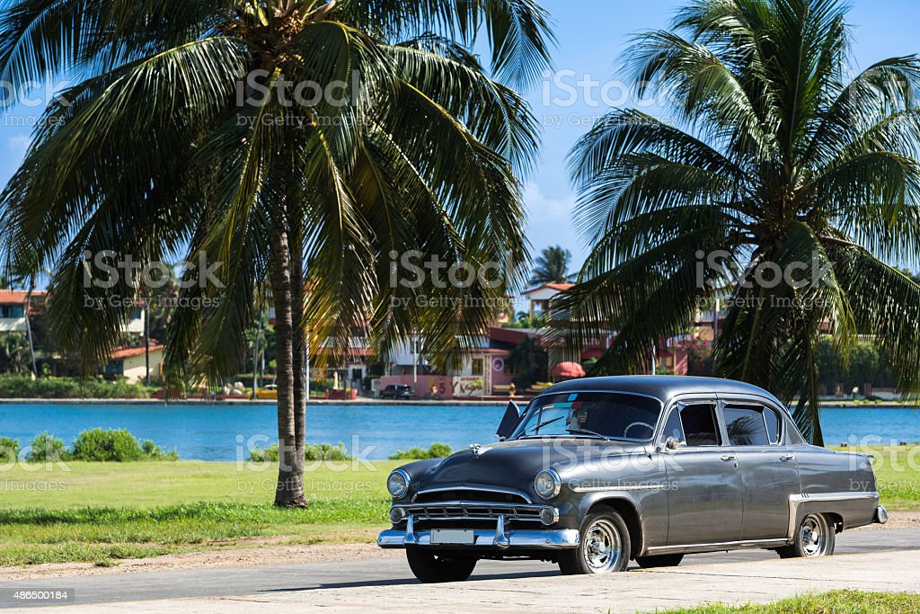 Classic american car parked under palms in Varadero Cuba stock photo
