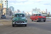 Classic American vehicles driving on the street in Havana