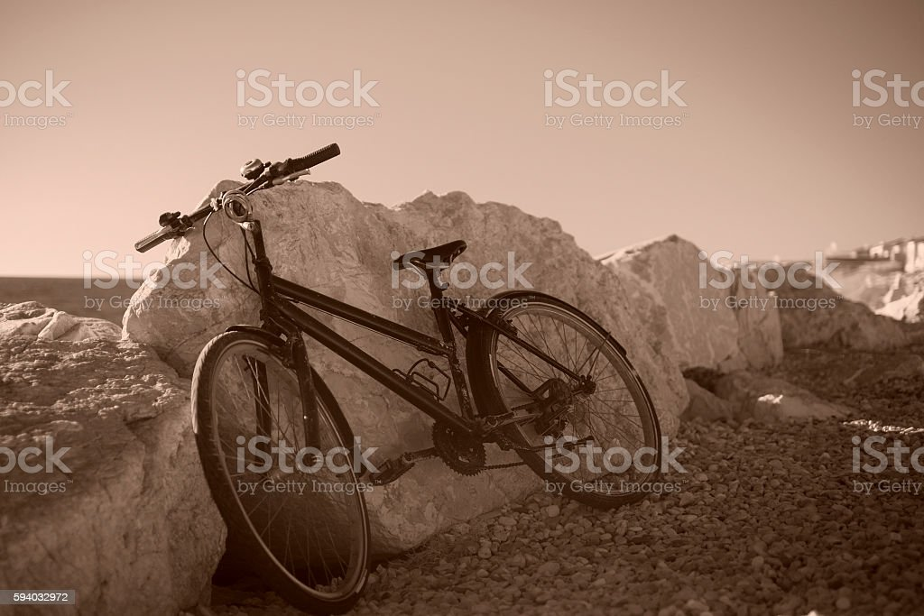 Classic bicycle at the seafront. Sepia toned stock photo