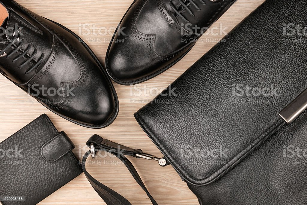 Classic black shoes, briefcase and purse on the wooden floor stock photo