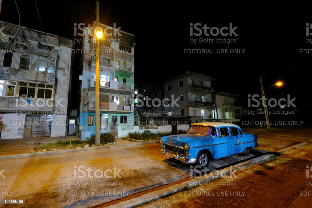 Classic blue car at night in front of apartments with street lights stock photo