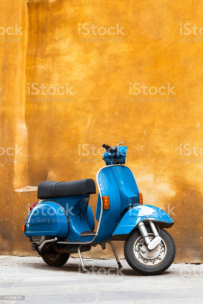Classic Blue Scooter Against Yellow Grunge Wall, Tuscany, Italy stock photo