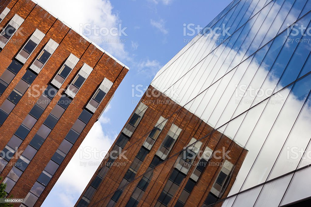 Classic Brick Building Reflected In Modern Glass Office stock photo
