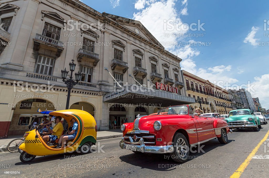 Classic car and Cocotaxi in Cuba stock photo
