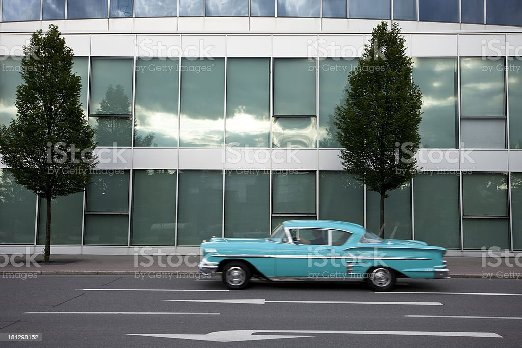 Classic Car Driving Past Modern Office Building royalty-free stock photo